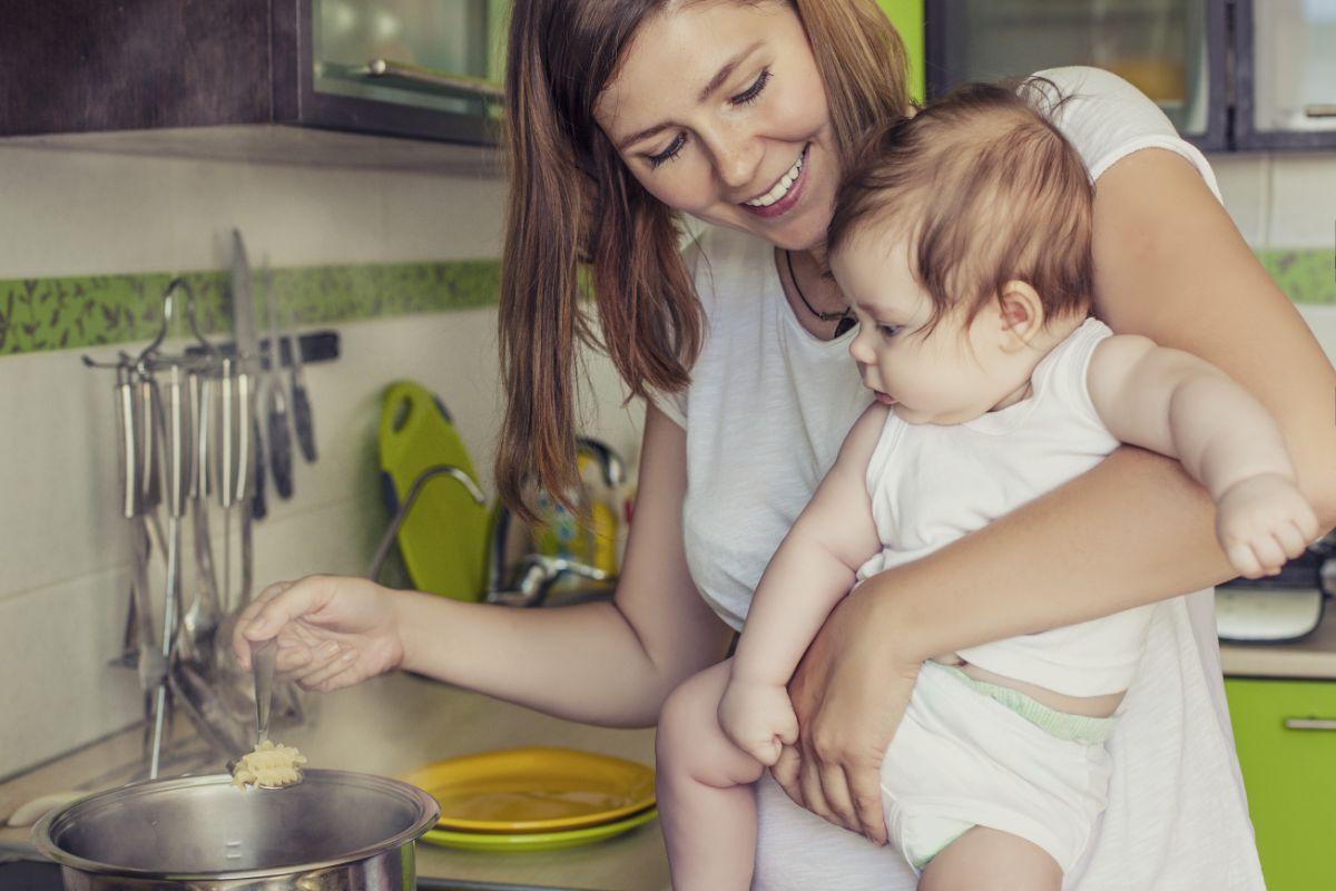 Madre con bebé cocinando alimentos