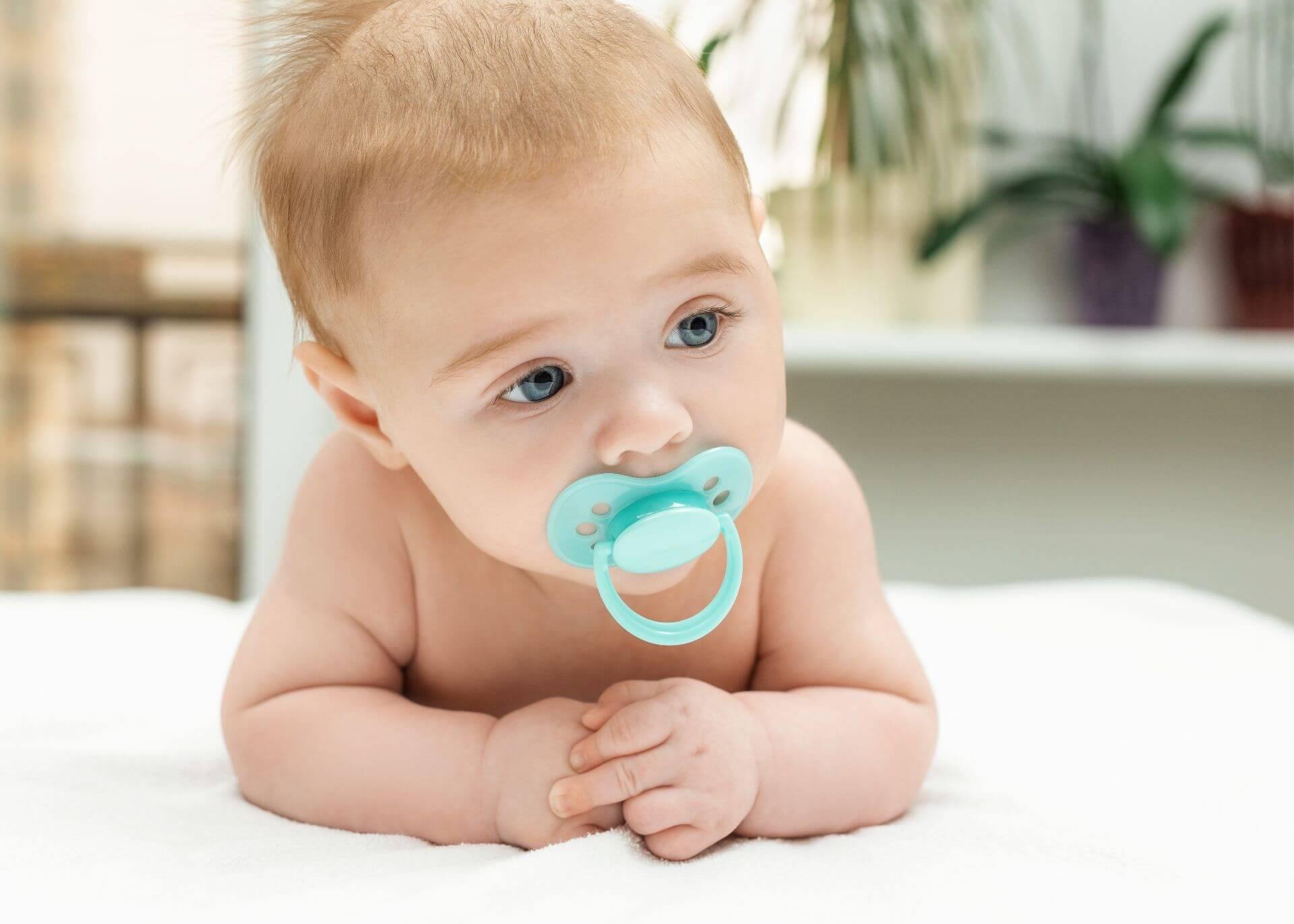 bebé con chupón celeste sobre una cama blanca