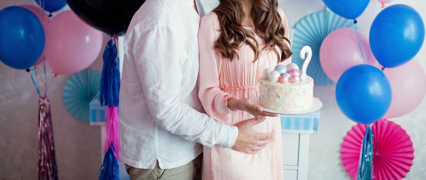 Madre embarazada junto a su pareja en una fiesta de gender reveal con globos y pastel