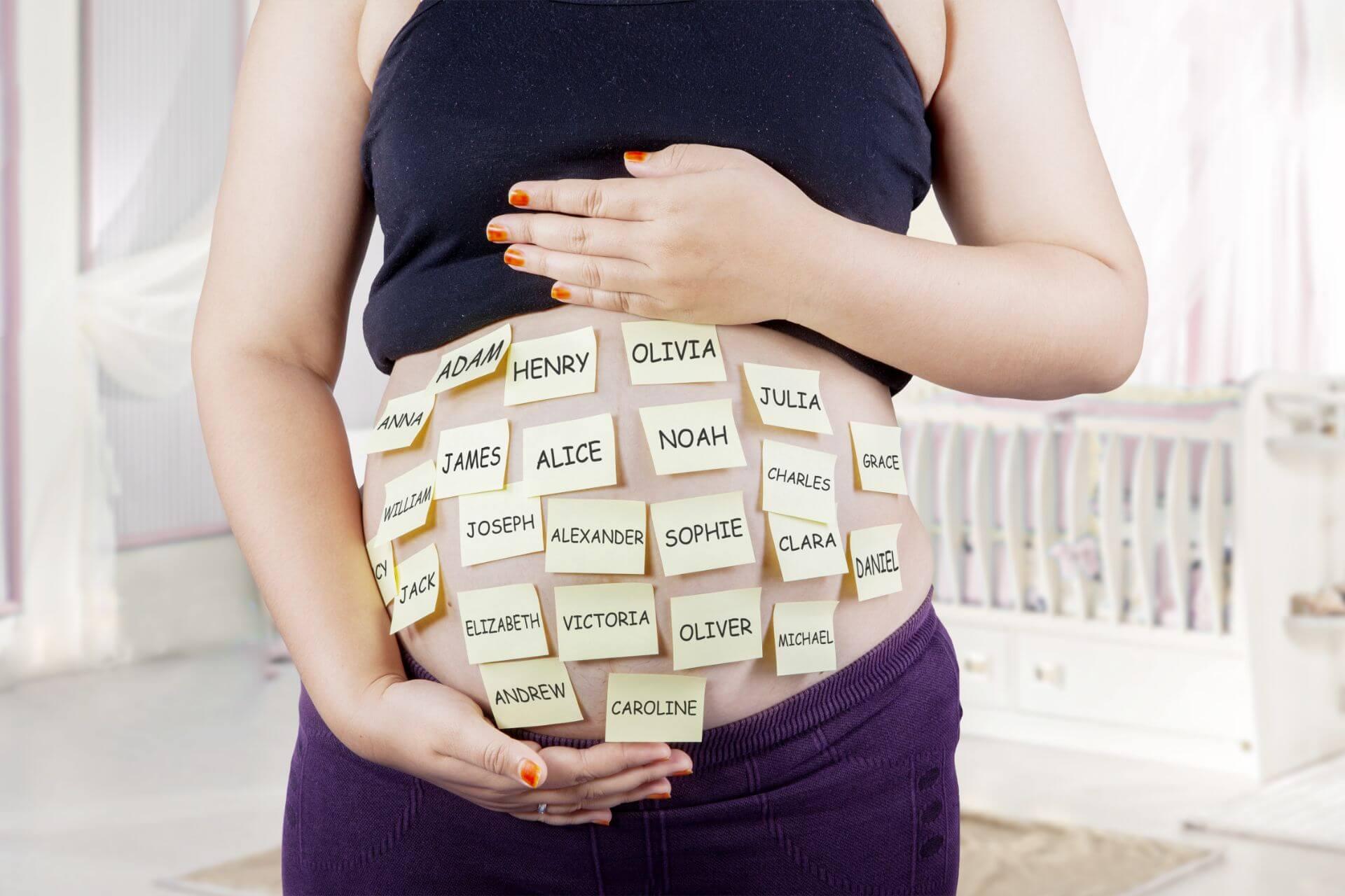 Mujer embarazada con nombres de bebé en su panza