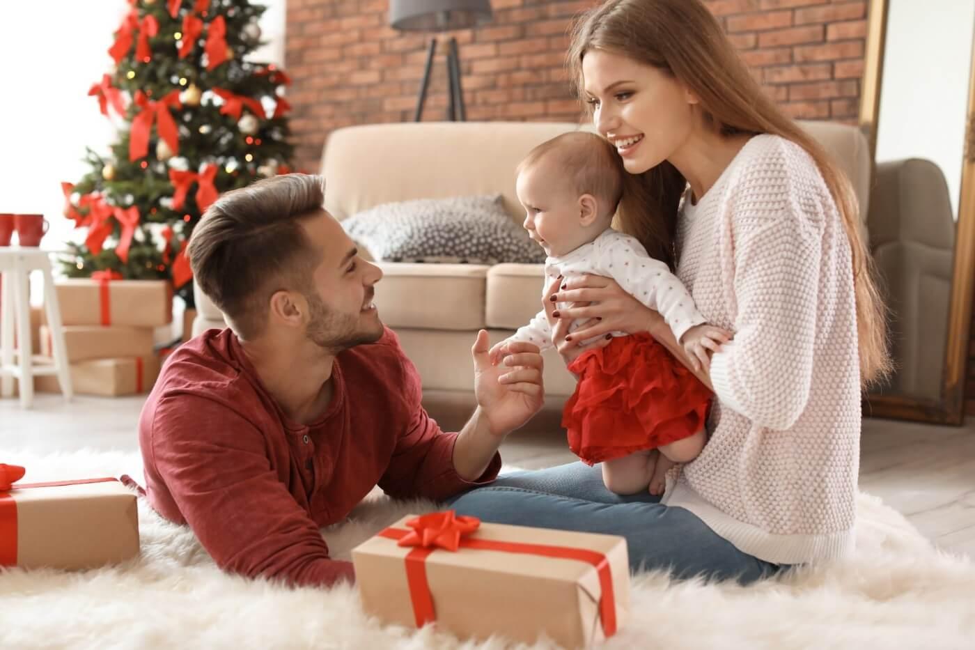 padres abriendo regalos de navidad con su bebé recién nacido